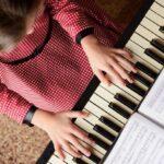 : Seorang anak perempuan yang sedang memainkan sebuah lagu dengan menggunakan piano.