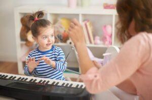 Guru yang sedang mengajarkan si kecil bermain piano
